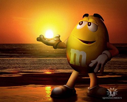 Желтый M&M's на фоне морского заката